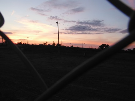 Beyond the chain link fence where I work a cosmic sunset dwarfs my workplace - Jan. 13, 2013